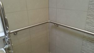 STAINLESS STEEL HANDRAIL FORMED TO FIT A CORNER OF THE BATHROOM